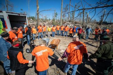 Volunteers join to pray at one of our work sites.