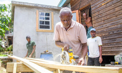 Sawdust flies as men with the apprenticeship program work to construct storm shutters.