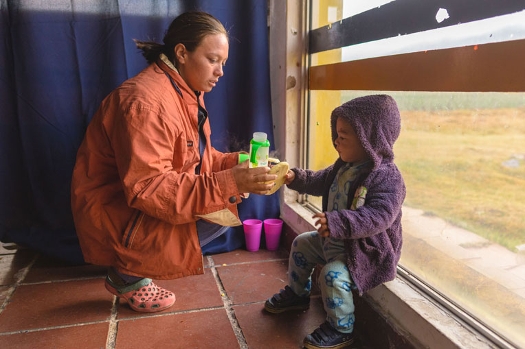 Angelica feeds her young son breakfast provided at our shelter in Berlin, Colombia.