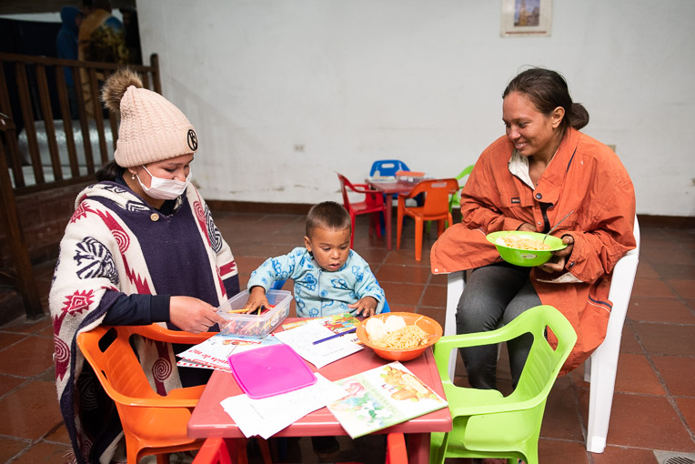 A Venezuelan mother (right) enjoys a meal with her young son at our shelter.