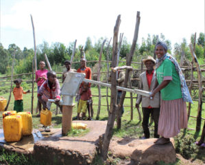 Residents in Korido test out the repaired water pump that's recently made water available to them again.