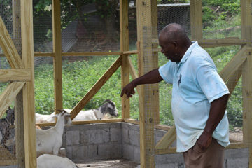 Kenneth points out the chicken coop Samaritan's Purse equipped him to build while his goats also explore it.