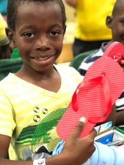 Duke had been hoping and praying for a pair of shoes. He received these red flip-flops in his shoebox.