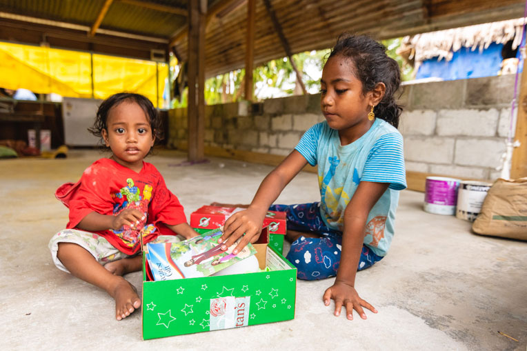 A girl shows her sister the shoebox gift she received during the outreach event in her village.