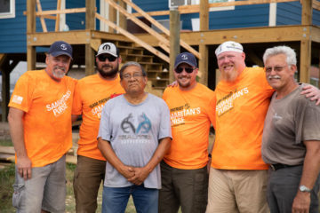 Brandon, far right, and Team Patriot members with homeowner Manuel.