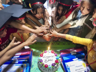 Children and their families enjoy graduation cake.