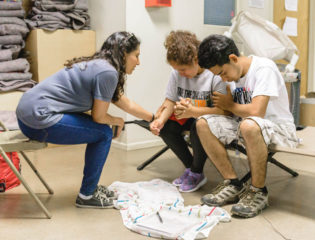 One of our staff prays with a migrant woman and her son at the shelter in Del Rio.