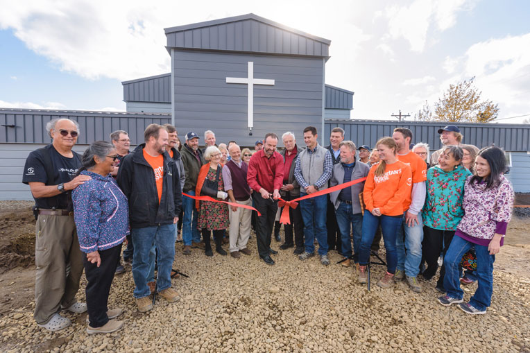 Simon Flynn, pastor of Dillingham Moravian Church, cuts the ribbon during a dedication of the church's new building last week.