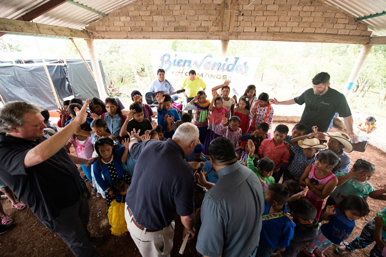 Children, church leaders, and Edward Graham gather in prayer during the church dedication.