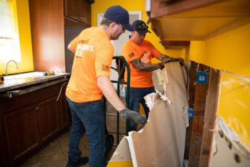 Volunteers work to remove damaged sheetrock.