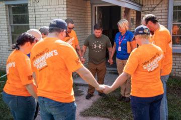 AJ prays with Team Patriot volunteers.