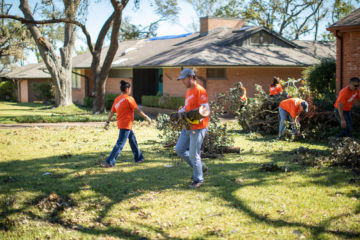 Volunteers clear trees and debris from yards near Dallas, Texas, where an EF3 tornado and other twisters tore through communities.