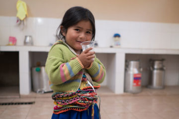 Maria enjoys freshly pasteurized milk at the dairy processing center.