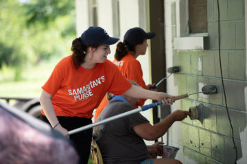 Teams of Samaritan's Purse volunteers paint the exterior of Miss Angel's new home.