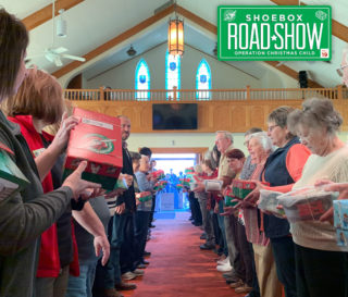 Participants from more than 25 different churches line the center aisle of First Baptist in Belle, Missouri, to pray over the shoebox gifts they packed.