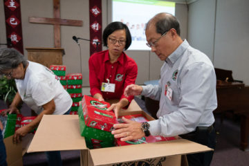 Manny Ma and his wife Wen Li place Operation Christmas Child gift-filled shoeboxes into a carton for shipment to children in need overseas.