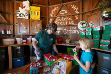Jana Ginter and a young friend from Golden Prairie Church prepare shoeboxes for kids in need overseas.