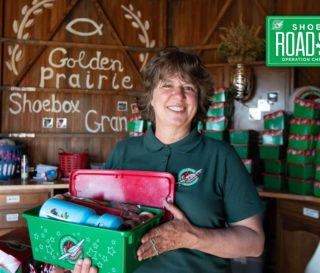 Jana Ginter proudly displays a gift-filled Operation Christmas Child shoebox she packed in her refurbished granary.