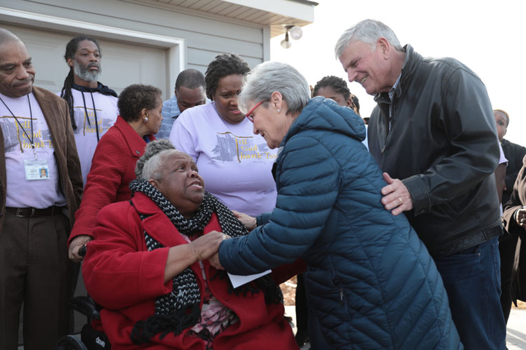 Franklin and Jane Graham greet Earnestine Reese at the home dedication on Dec. 20.