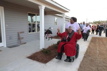 Earnestine celebrates outside her new home.