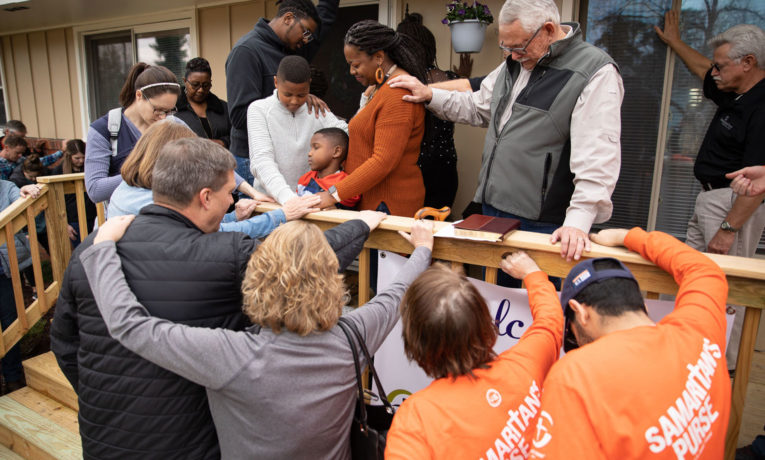 Samaritan's Purse staff and volunteers pray over the newly-rebuilt home of Army Sergeant Anthony and Kenyatta James in New Bern, North Carolina.