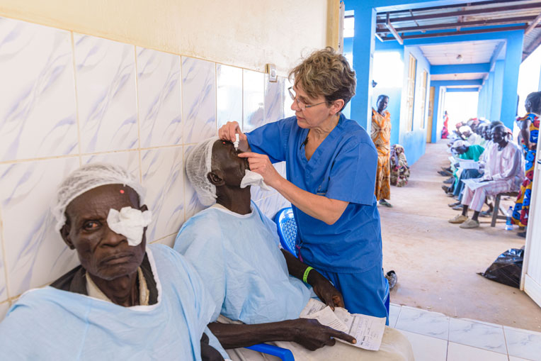 Patients receive eye drops as they are prepped for surgery.