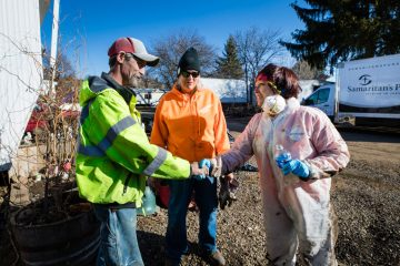 Homeowner Robert Warden meets with some of the volunteers who helped clean mud and debris out of his home.