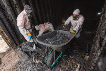 Amy and Mike (center and right) help sift through the ashes in search of a homeowner's personal belongings.