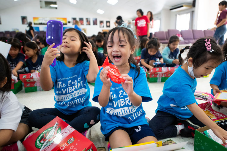 Children celebrate the special shoebox gifts they received at the Operation Christmas Child outreach event.