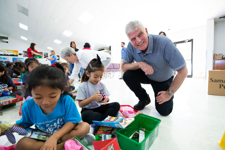 Samaritan's Purse President Franklin Graham joins children opening their gifts.