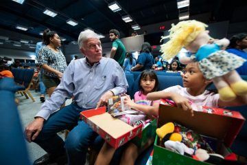 Franklin Graham watches as a young girl discovers a special doll in her shoebox.