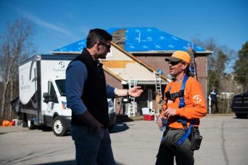 Edward Graham speaks with a Samaritan's Purse volunteer in front of a home we tarped.