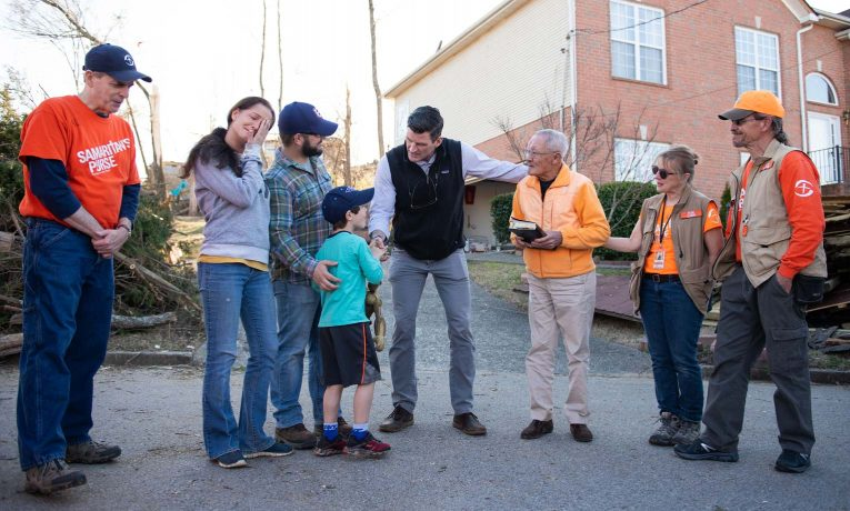 Edward Graham and Samaritan's Purse volunteers pray with homeowners, the Scarfia family and Canh Dang Duc.