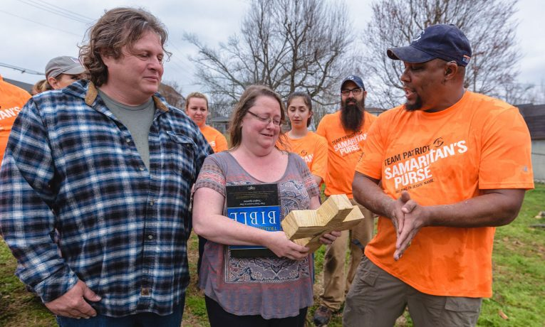 Marine Sergeant Robert Bogus presents a Bible and also a chainsaw-cut cross to homeowners Christy and Travis Autry.