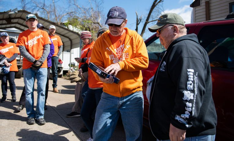 Samaritan's Purse volunteers present Mike Worrell, right, with a Bible signed by those who worked on his property.