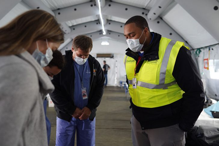 Chaplains and medical staff pray just before receiving patients.