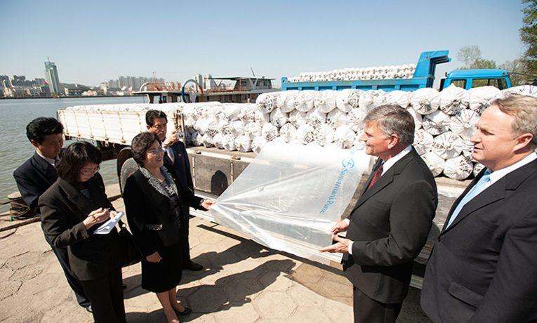 On behalf of Samaritan's Purse, Franklin Graham delivers rolls of plastic sheeting to the city of Sinjiju, across the river from Dandong, China. The sheeting helped farmers protect seedlings from cold weather during early planting.