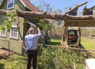Franklin Graham met volunteers working hard to remove trees and other debris from homes.