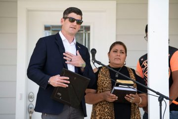 Edward Graham presents Francisca Castañeda and her son Jose with a special Bible and a key to their new home.