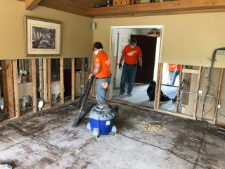 After pulling out flooring and removing portions of ruined walls, volunteers vaccuum any remaining debris.