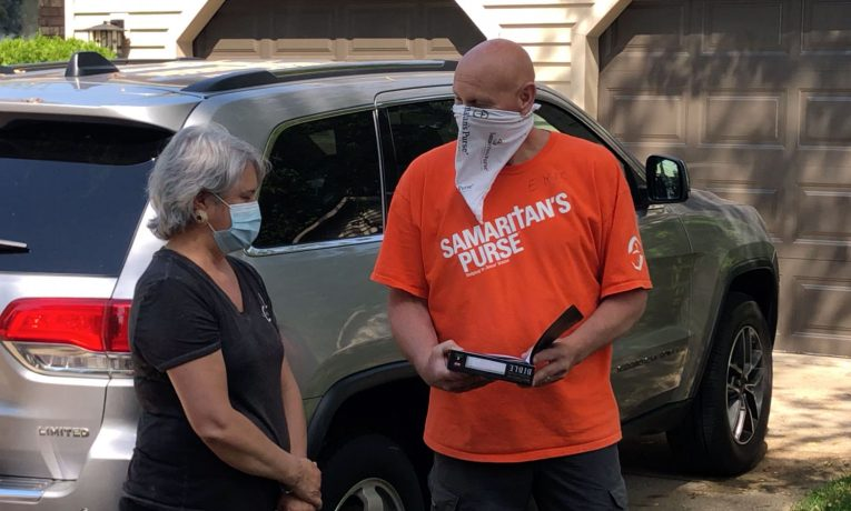 A volunteer presents a homeowner with a special Billy Graham Study Bible signed by the team.