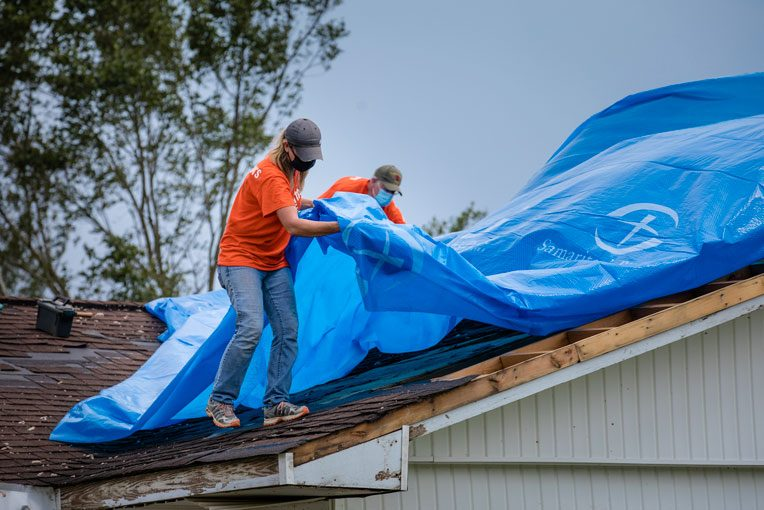 Volunteers tarp the roof of the Tate's home.
