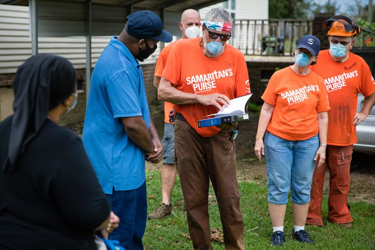 Volunteers present a Bible to Coella and Manley Tate signed by everyone who worked on their home.
