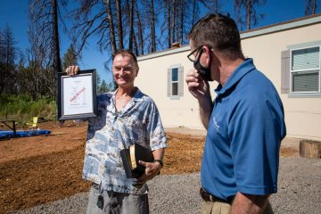 """Teddy Glaum holds up a """"Paid in Full"""" notice from Bruce Poss, Samaritan's Purse director of Samaritan's Purse North American Ministries."""