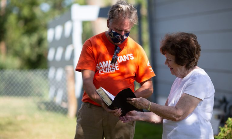 Volunteers presented homeowner Della Ramsey with a Billy Graham Study Bible signed by the team after clean up work was completed at her house.