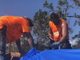 Volunteers work hard to tarp the roof at Rafe David's home.