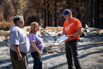 Dan and Rochelle receive a Bible signed by all the volunteers who worked on their property.