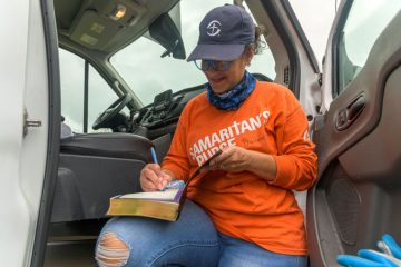 Bonnie signs the inside cover of a Bible the team gave the homeowners.