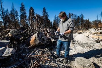 Stephen MacAulay surveys the ruins and ashes of his property where Samaritan's Purse volunteers are helping him recovery belongings.