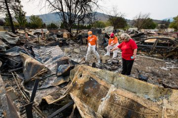 Paula Vessels shows volunteers through the burned remains of her home as they search for treasured belongings buried in the ashes. She is hopeful they'll find, among other valuables, military medals belonging to her late brother.